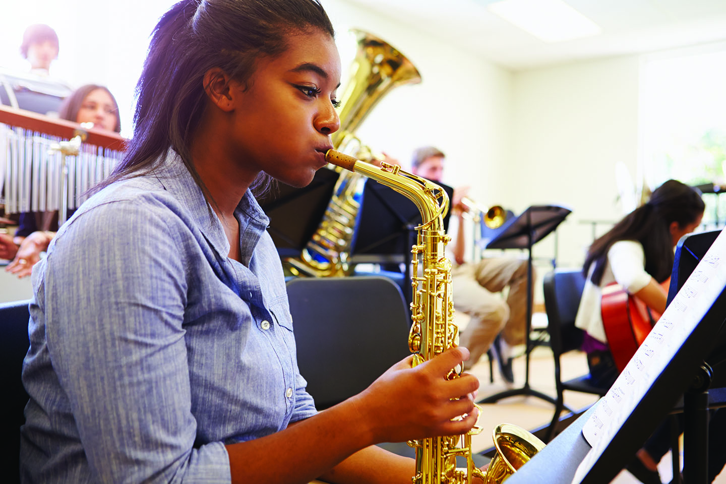 A young girl playing the saxophone